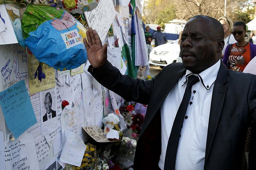 "A well-wisher prays outside the hospital where former South African President Nelson Mandela is being treated at in Pretoria on July 17, 2013. Mr Mandela will spend his 95th birthday in hospital on Thursday, but was said to be making ""remarkable"" pro"