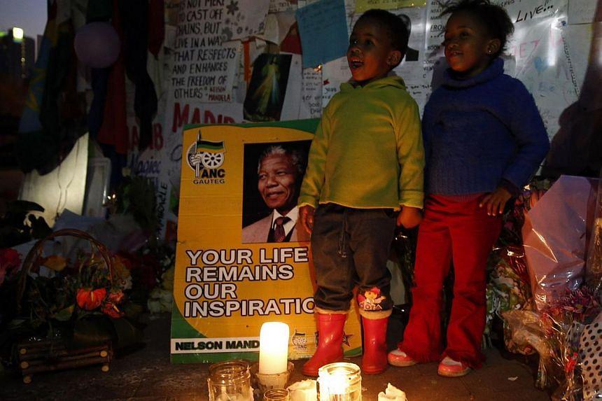 Children sing Happy Birthday in front of messages of support outside the hospital where former South African President Nelson Mandela is being treated at in Pretoria on July 17, 2013. Mr Mandela will spend his 95th birthday in hospital on Thursday, b