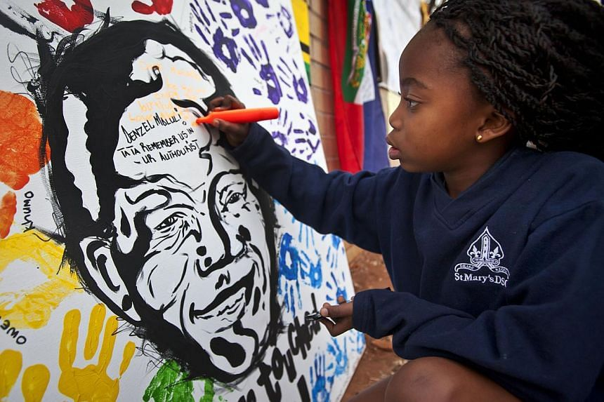 Ayanda Mkhize, 7, writes a get-well message on a painting of Nelson Mandela made by another class at the St Mary's Diocesan School for Girls and left outside the Mediclinic Heart Hospital, where former South African President Nelson Mandela is being
