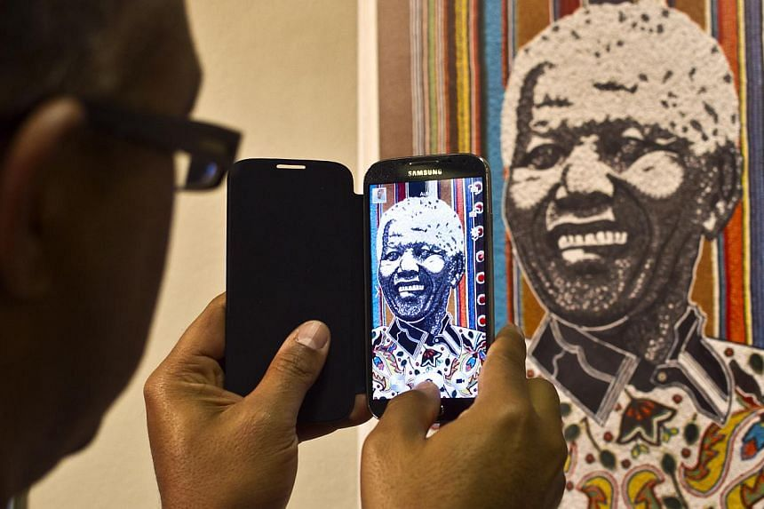 A visitor uses his phone to take a photo of one of the posters at the opening of an international exhibition of 95 posters from around the world celebrating the 95 years of the life of former South African President Nelson Mandela, at the University