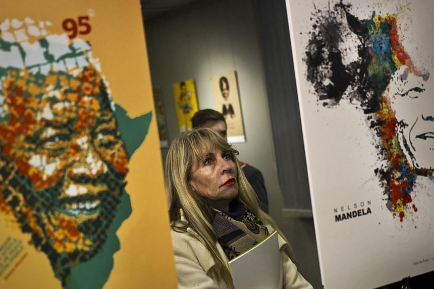 A visitor observes posters at the opening of an international exhibition of 95 posters from around the world celebrating the 95 years of the life of former South African President Nelson Mandela, at the University of Pretoria in South Africa on July