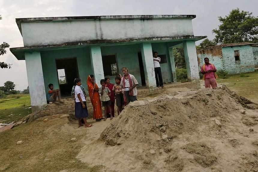 Villagers in front of a school stand next to the grave of a child who died after consuming contaminated meals given to children at a school on Tuesday, July 16, 2013, at Chapra district in the eastern Indian state of Bihar on Thursday, July 18, 2013.