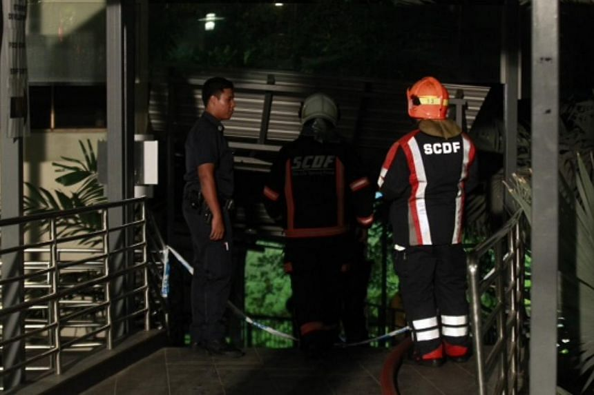 Police and Singapore Civil Defence Force personnel at the scene of the fire at a food court in Singapore Polytechnic. -- ST PHOTO: KEVIN LIM
