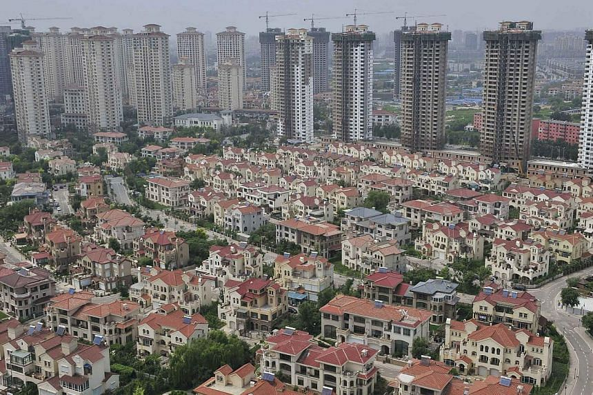 A block of villa residences is seen in front of new residential buildings under construction in Shenyang, Liaoning province on Thursday, July 18, 2013. The pace of China's month-on-month home price rises edged down for a third straight month in June,