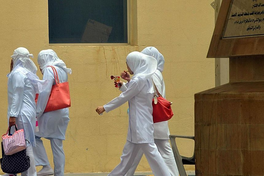 Staff nurses walk towards the King Fahad hospital in the city of Hofuf, 370km east of the Saudi capital Riyadh, on June 16, 2013. The World Health Organisation on Wednesday held off from calling for travel restrictions related to the Middle East resp