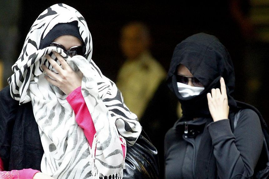 Hostesses Lisa (left) and Chanel, who had entertained the linesmen involved in a football match-fixing case, testified on Thursday, July 18, 2013, that the men did not pay them for the sexual services. -- ST PHOTO: WONG KWAI CHOW