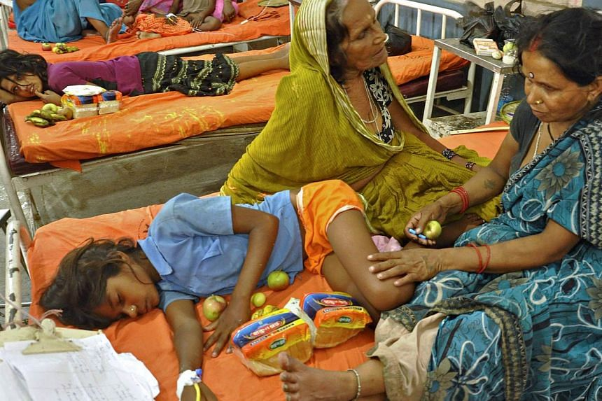 Indian schoolchildren, who consumed a free meal at a school in the Saran district of Bihar state, recuperate at a ward after receiving fruits and bread at the Patna Medical College and Hospital in Patna on Thursday, July 18, 2013. Thousands of school