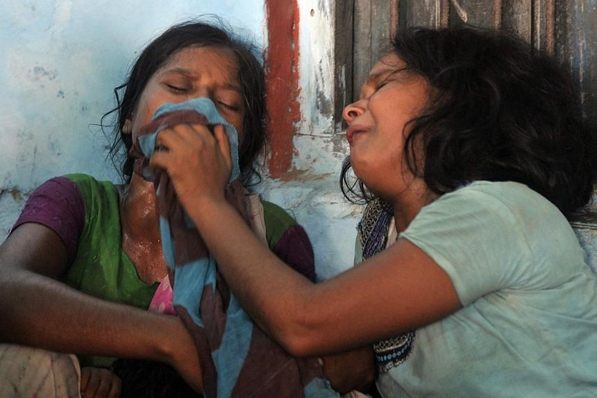 Women mourn the death of their children who died after consuming contaminated meals given to children at a school on Tuesday at Chapra in the eastern Indian state of Bihar on Wednesday, July 17, 2013. The state government revealed plans to pay compen