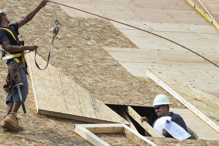Workers complete the final phases of a roof on a new townhouse under construction in Ashburn, Virginia, on Sept 7, 2012. United States housing starts and permits for future home construction unexpectedly fell in June, but the decline in activity
