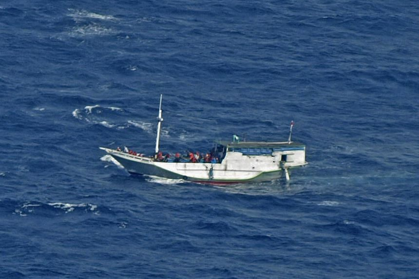 In this July 4, 2012 photo released by the Indonesian National Search and Rescue Agency, a wooden boat which is believed to have up to 180 asylum seekers on board floats on the waters off Christmas Island, Australia.Australia plans to resettle