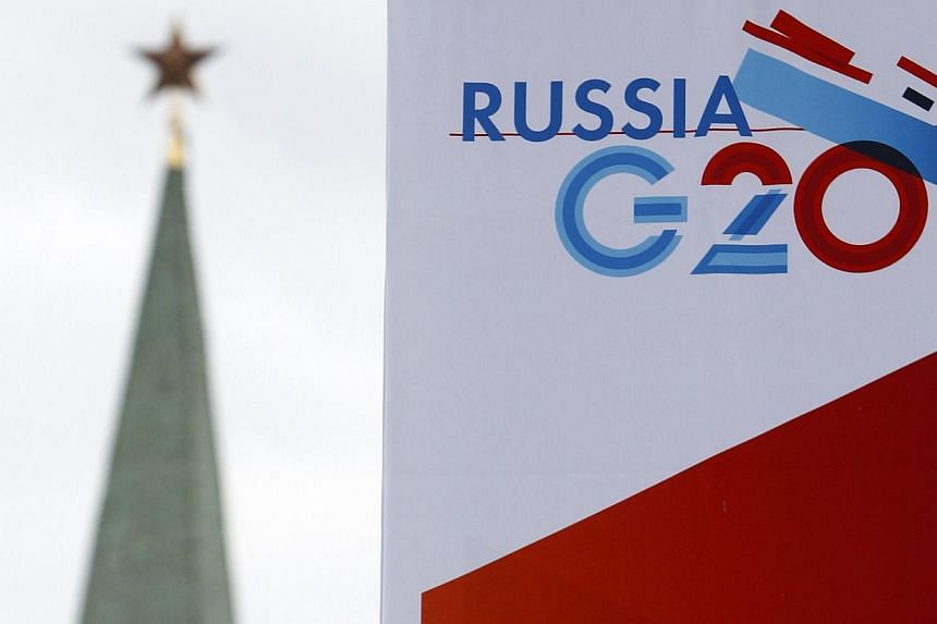 A tower of the Kremlin is seen behind a sign hanging on the Manezh Exhibition Center, venue for this week's meeting of G20 finance ministers, in Moscow on July 16, 2013. Finance ministers and central bankers from G20 countries meet in Moscow for a tw