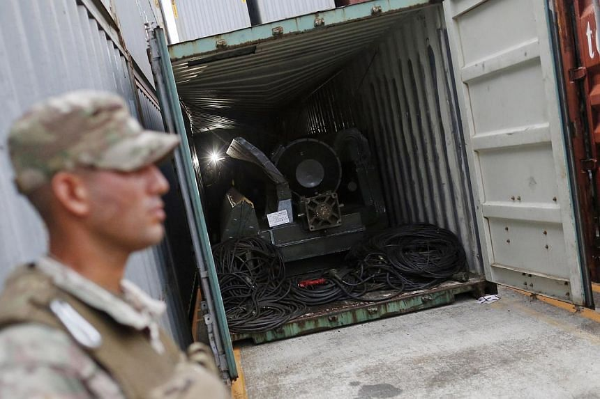 """A police officer stands guard at a container holding arms seized from the North Korean flagged ship """"Chong Chon Gang"""" at the Manzanillo Container Terminal in Colon City on July 17, 2013. UN sanctions experts will go to Panama soon to investigate a No"""