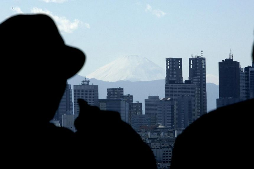 Visitors look towards buildings and at Japan's Mt. Fuji from an observatory in Tokyo on Feb 15, 2007. Property developers in greater Tokyo sold 81.6 per cent of new apartments they brought to market in June, the Real Estate Economic Institute Co, an
