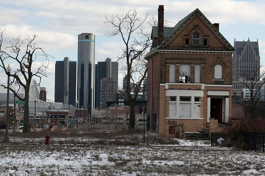 A vacant, boarded up house is seen in the once thriving Brush Park neighbourhood with the downtown Detroit skyline behind it in Detroit, Michigan, on March 3, 2013. Detroit filed the largest-ever municipal bankruptcy in United States (US) histor