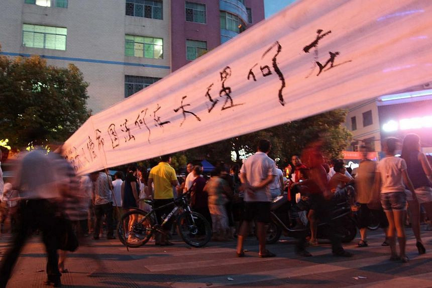 People gather on a street to protest after a fruit seller, Deng Zhengjia, died in Linwu county, central China's Hunan province on Wednesday, July 17, 2013. Six Chinese local government employees involved in a dispute that saw a roadside watermelon se