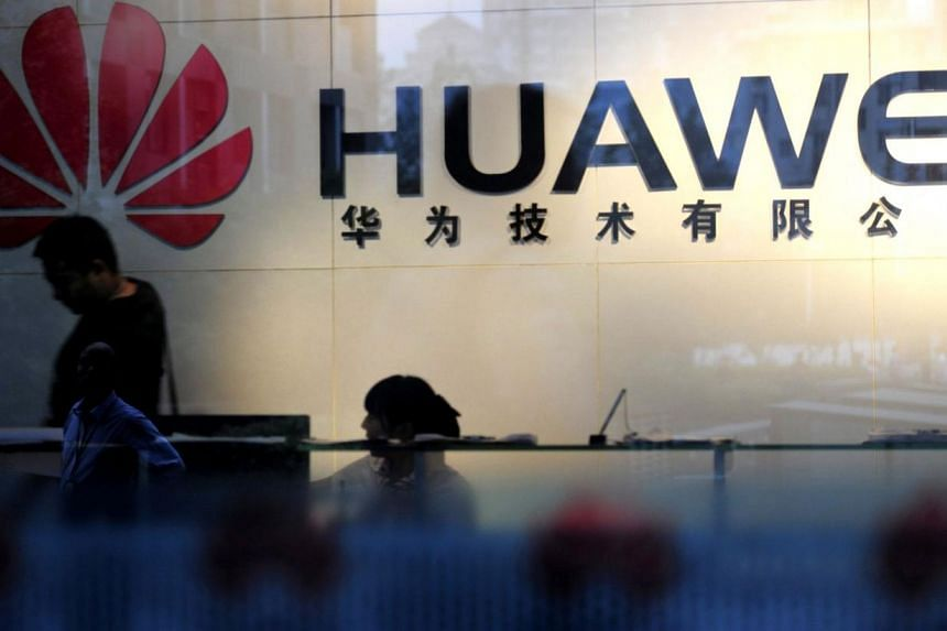 Staff and visitors walk pass the lobby at the telecommunications equipment firm Huawei Technologies in Wuhan, central China's Hubei province on Oct 8, 2012. The former head of the United States' Central Intelligence Agency Michael Hayden said on Frid