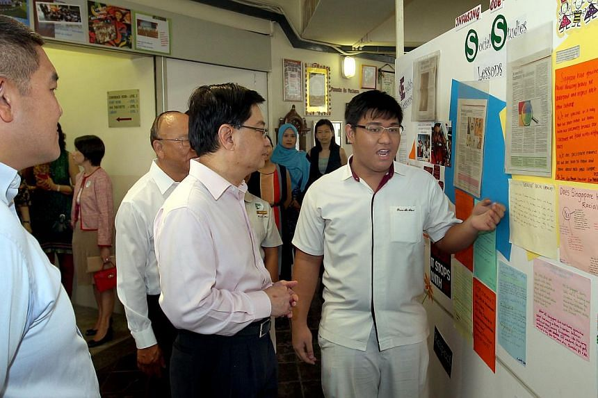 (From left) Prinicipal of Pioneer Secondary School Mr Mark Chan Weng Kit, School Advisory Committee Chairman Mr Ang Chee Guan and Education Minister Heng Swee Keat watch as Student Manval Papa Manuntag, 17, explains his exhibit in Pioneer Secondary S