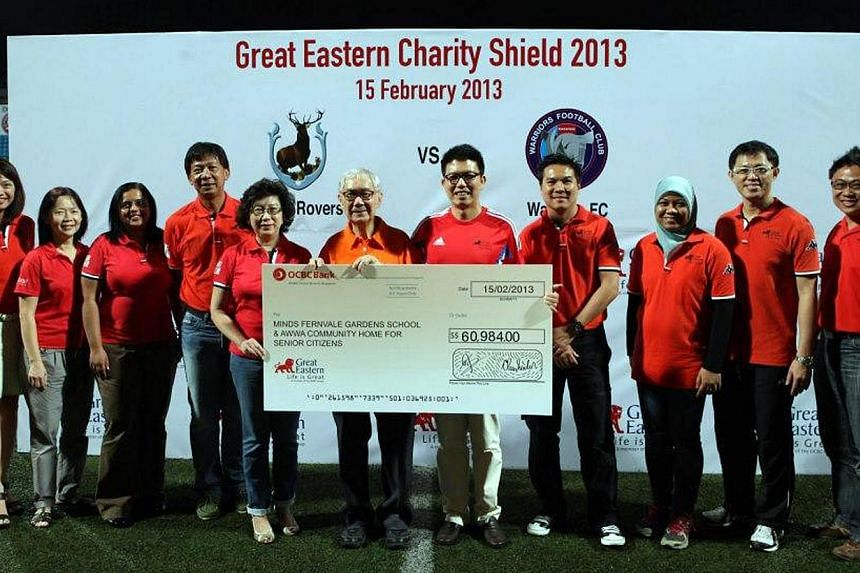 (From fourth left) S-League CEO Lim Chin, Great Eastern's head of group corporate communications Ms Tan Seck Geok, Community Chest's vice-chairman Mr Hwang Peng Yuan, Great Eastern's chief marketing officer Mr Colin Chan pose with other staff w