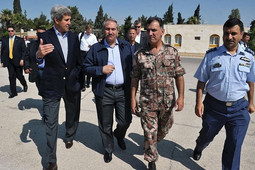 US Secretary of State John Kerry (left) and Jordanian Foreign Minister Nasser Judeh (second left) are escorted by military officers at Marka airport in Amman, Jordan on Thursday, July 18, 2013, before boarding a helicopter bound for the Zaatari refug