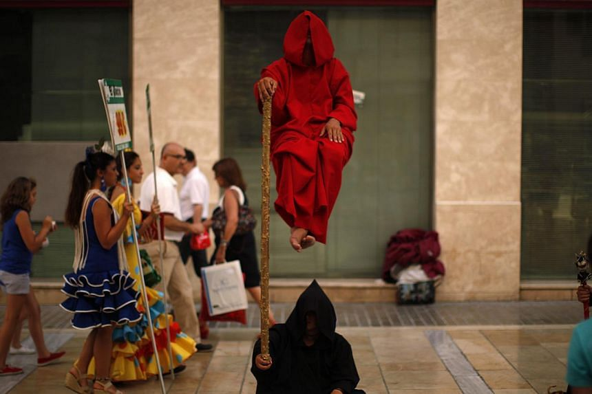 Women wearing traditional Sevillana dresses (left) walk past street performers at Marques de Larios street in downtown Malaga, southern Spain on Thursday, July 18, 2013. -- PHOTO: REUTERS