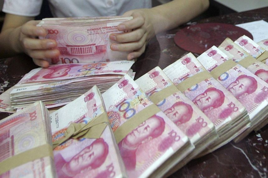 An employee counts Chinese 100 yuan banknotes at a branch of Bank of Communications in Shenyang, Liaoning province on July 6, 2012. China's central bank announced long-awaited interest rate reforms on Friday, July 19, 2013, removing controls on the r