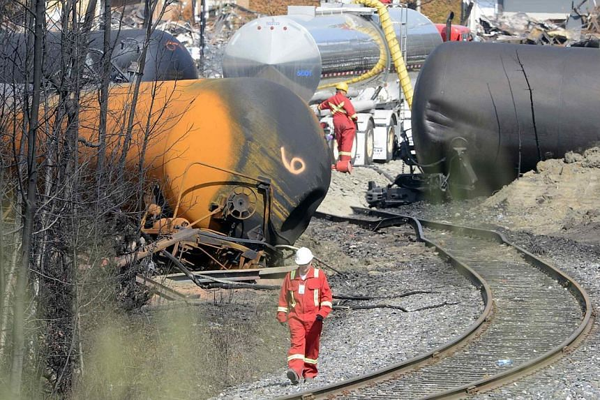 A worker walks near the railway track on the site of the train wreck in Lac Megantic on July 16, 2013. Canada's two big railroads are reviewing safety standards after the deadly train crash on July 6 that killed some 50 people. -- FILE PHOTO: REUTERS
