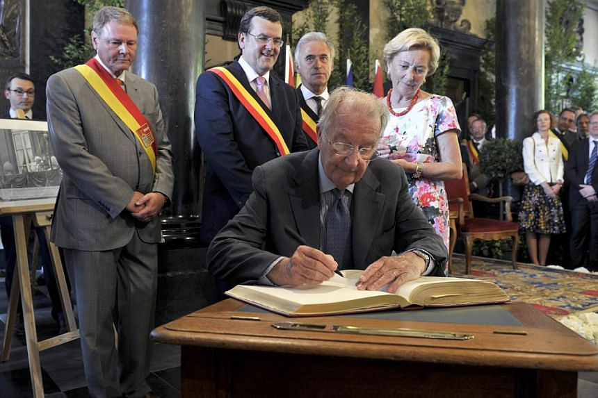 Belgium's King Albert II signs the golden book of the townhall as and Queen Paola looks on while visiting the city of Liege on July 19, 2013. The monarchy, along with soccer and beer, is viewed as one of the rare things that unify linguistically divi