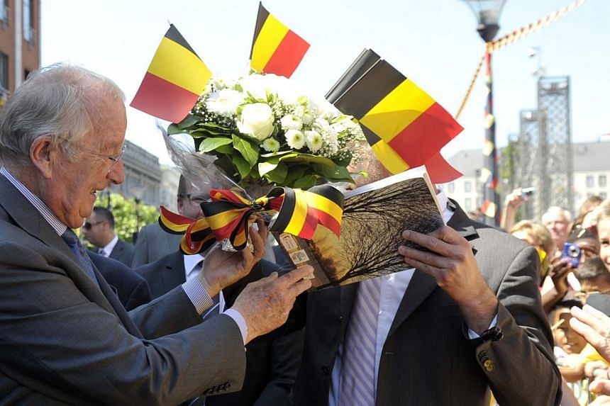 Belgium's King Albert II greets people while visiting the city of Liege on July 19, 2013. The monarchy, along with soccer and beer, is viewed as one of the rare things that unify linguistically divided Belgium and when Prince Philippe becomes its new