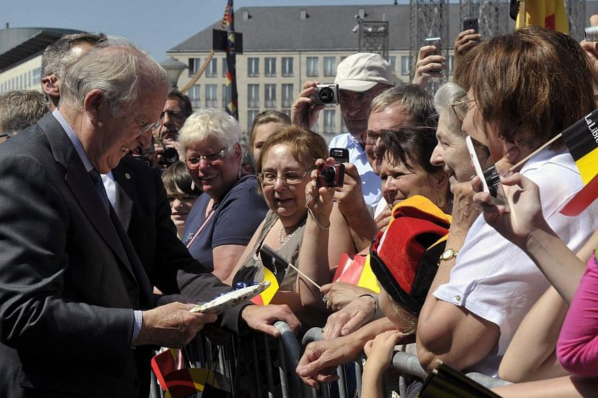Belgium's King Albert II (left) greets people while visiting the city of Liege on July 19, 2013. The monarchy, along with soccer and beer, is viewed as one of the rare things that unify linguistically divided Belgium and when Prince Philippe becomes