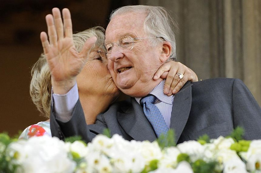 King Albert II of Belgium and Queen Paola of Belgium wave during a visit of the Belgian Royal couple in Liege on July 19, 2013. Queen Paola shed a tear on Friday after twice offering Albert II a kiss as the royal couple took a farewell tour of Liege
