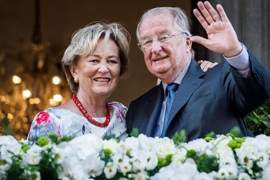 Belgium's King Albert II and Queen Paola wave to the crowd as they stand on the balcony of the City Hall in Liege, Belgium, during the last day of their 3-day farewell tour on Friday, July 19, 2013. In a fractious nation ever more divided by language