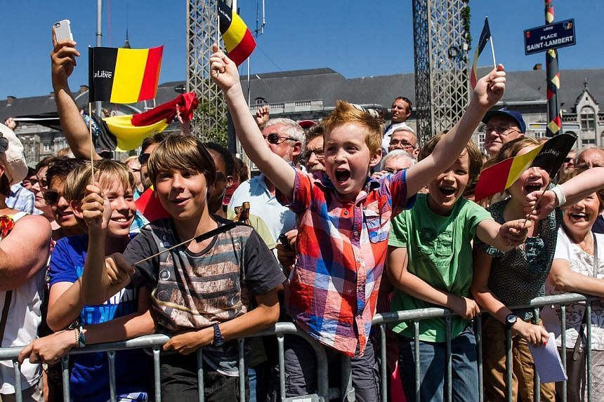 Fans of the Belgian Royals wave Belgian flags and shout royalist slogans to the Belgian Royals during the last day of their 3-day farewell tour in Liege, Belgium, on Friday, July 19, 2013. In a fractious nation where even the monarchy is a fraying sy