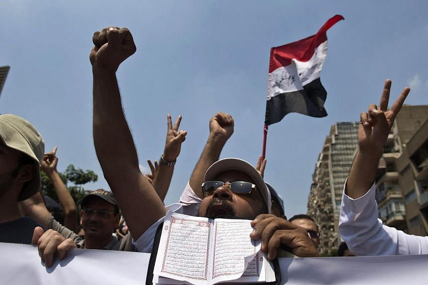 A supporter of the Muslim Brotherhood and ousted Egyptian president Mohamed Morsi holds a Koran, Islam's holy book, as he shouts slogans with fellow protesters marching towards Cairo University to demand his reinstatement in Cairo on July 19, 2013. -