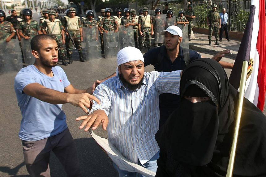 Supporters of Egypt's ousted President Mohammed Morsi push back a protester who tried to reach a cordon of Egyptian army soldiers, during a demonstration near the Republican Guard headquarters, in Cairo, Egypt, on Friday, July 19, 2013. -- PHOTO: AP