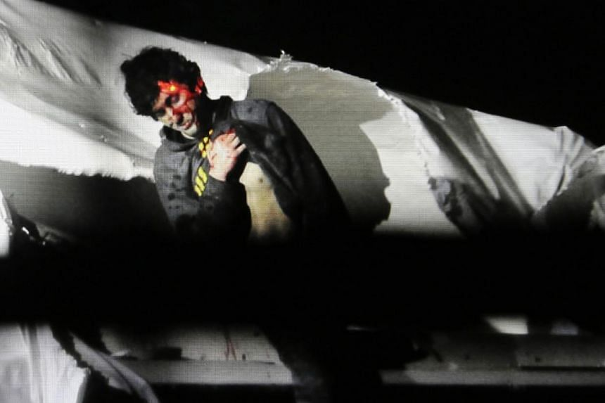 Massachusetts State Police photo, 19-year-old Boston Marathon bombing suspect Dzhokhar Tsarnaev, bloody and disheveled with the red dot of a sniper's rifle laser sight on his head, emerges from a boat at the time of his capture by law enforcement aut
