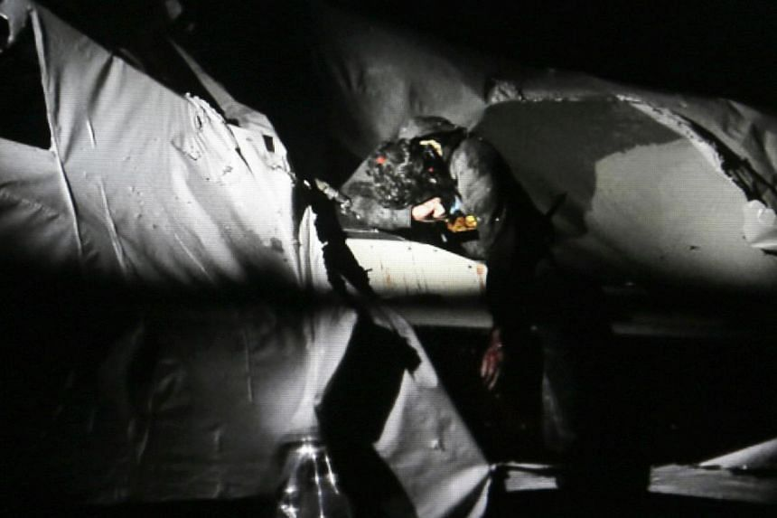 Massachusetts State Police photo, 19-year-old Boston Marathon bombing suspect Dzhokhar Tsarnaev, with the red dot of a sniper's rifle laser sight on the top of his head, leans over a part of a boat where he had been hiding moments before his capture