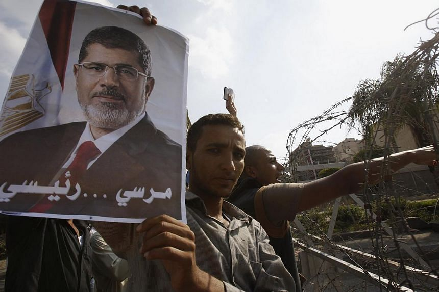 A member of the Muslim Brotherhood and supporter of deposed Egyptian President Mohamed Mursi holds up a poster of Mursi behind barbed wires outside the Republican Guard headquarters in Cairo on July 19, 2013. -- PHOTO: REUTERS