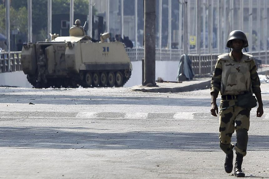 A soldier takes his position in front of members of the Muslim Brotherhood and supporters of deposed Egyptian President Mohamed Mursi at Republican Guard headquarters in Nasr City, a suburb of Cairo on July 19, 2013. -- PHOTO: REUTERS