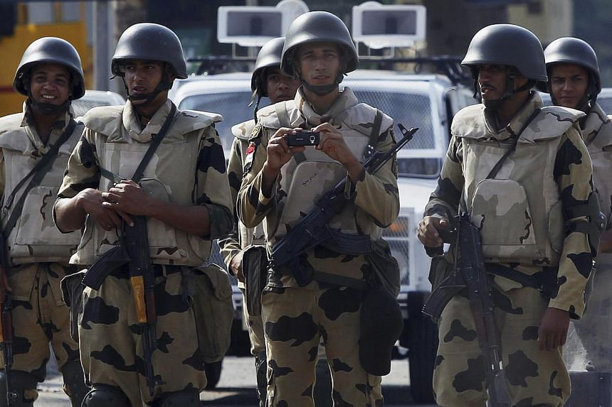 A soldier takes pictures, as he stands guard with his comrades, in front of members of the Muslim Brotherhood and supporters of deposed Egyptian President Mohamed Mursi at Republican Guard headquarters in Nasr City, a suburb of Cairo on July 19, 2013