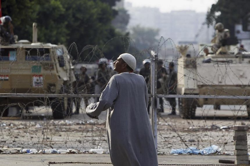 A supporter of deposed Egyptian President Mohamed Mursi stands near barbed wire in front of soldiers at the Republican Guard headquarters in Nasr City, a suburb of Cairo on July 19, 2013.-- PHOTO: REUTERS