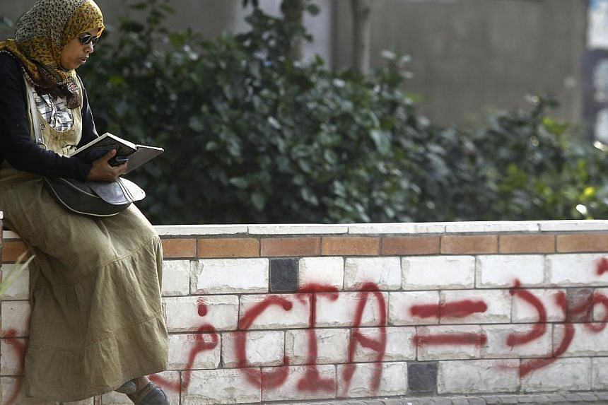 A member of the Muslim Brotherhood and supporter of deposed Egyptian President Mohamed Mursi reads the Koran, near graffiti criticising the Tamarud youth movement, in front soldiers at the Republican Guard headquarters in Nasr City, a suburb of Cairo