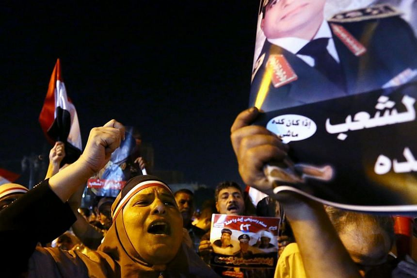 An Egyptian woman chants patriotic slogans on July 19, 2013 as she takes part in a demonstration with others to celebrate the 40th anniversary of the six day war against Israel in Cairo's landmark Tahrir square. -- PHOTO: AFP