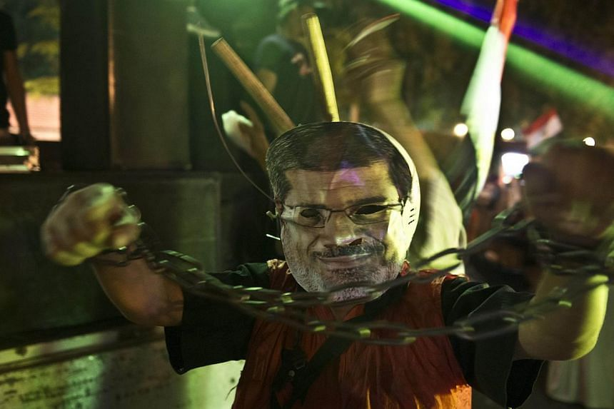 An man wearing a mask of ousted president Mohamed Morsi shows his handcuffed hands outside the presidential palace in Cairo on July 19, 2013, while opponents of ousted president Mohamed Morsi gather to celebrate the 40th anniversary of the six day wa