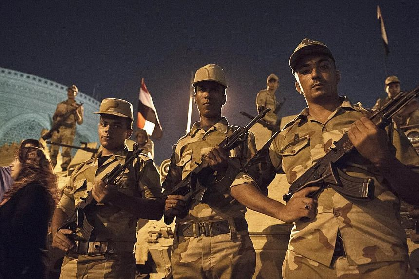 Egyptian soldiers stand in front of armoured vehicles outside the presidential palace in Cairo on July 19, 2013, while opponents of ousted president Mohamed Morsi gather to celebrate the 40th anniversary of the six day war against Israel. -- PHOTO: A
