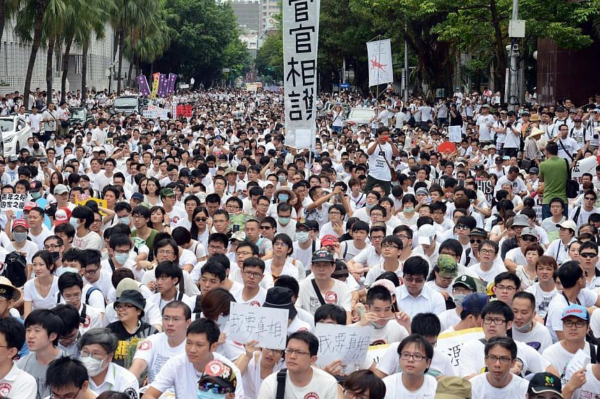 Protesters sit down during an anti-military rally outside the Defence Ministry in Taipei on July 20, 2013. Thousands of protesters rallied in Taipei on Saturday to demand justice for a corporal who died after allegedly being abused in the military, i