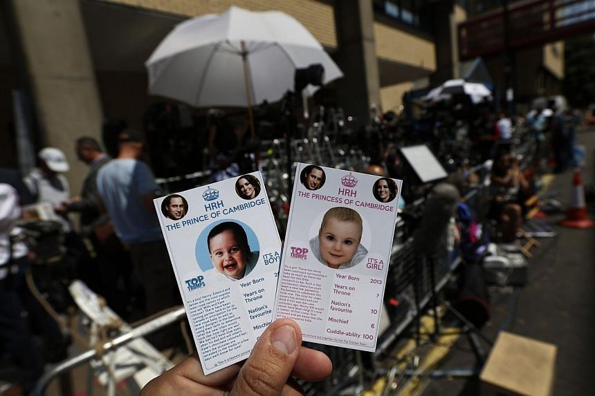 Cards of the royal baby, either as a boy or a girl, are specially made by a games company as a publicity stunt. In the background are members of the media waiting on Thursday, July 11, 2013, for the birth of the royal baby. -- PHOTO: AP