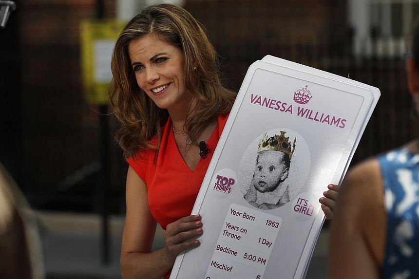 Broadcaster Natalie Morales of NBC holds placards made by a games company featuring guest co-host Vanessa Williams as a 'royal baby' during a live broadcast in London on Thursday, July 18, 2013. -- PHOTO: AP