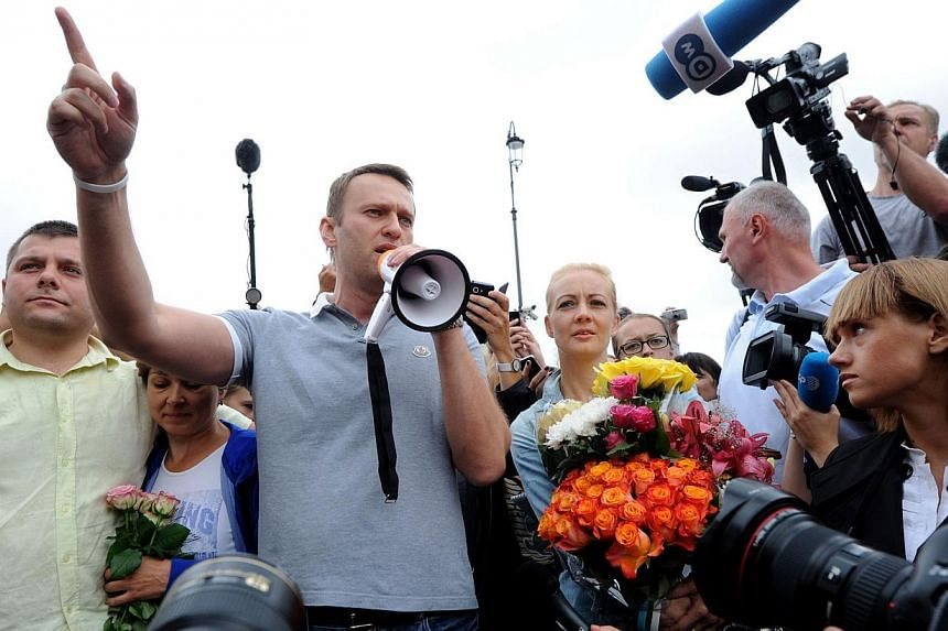 Russia's top opposition leader Alexei Navalny (centre) addresses supporters and journalists upon his arrival in a Moscow's railway station on Saturday, July 20, 2013. Mr Navalny told hundreds of cheering supporters on Saturday that he would push ahea