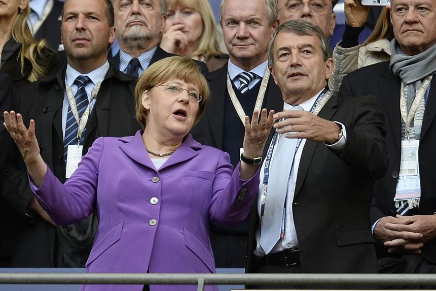 German chancellor Angela Merkel talks to German DBF President Wolfgang Niersbach (right) before the UEFA Champions League final football match between Borussia Dortmund and Bayern Munich at Wembley Stadium in London on May 25, 2013. German Football F