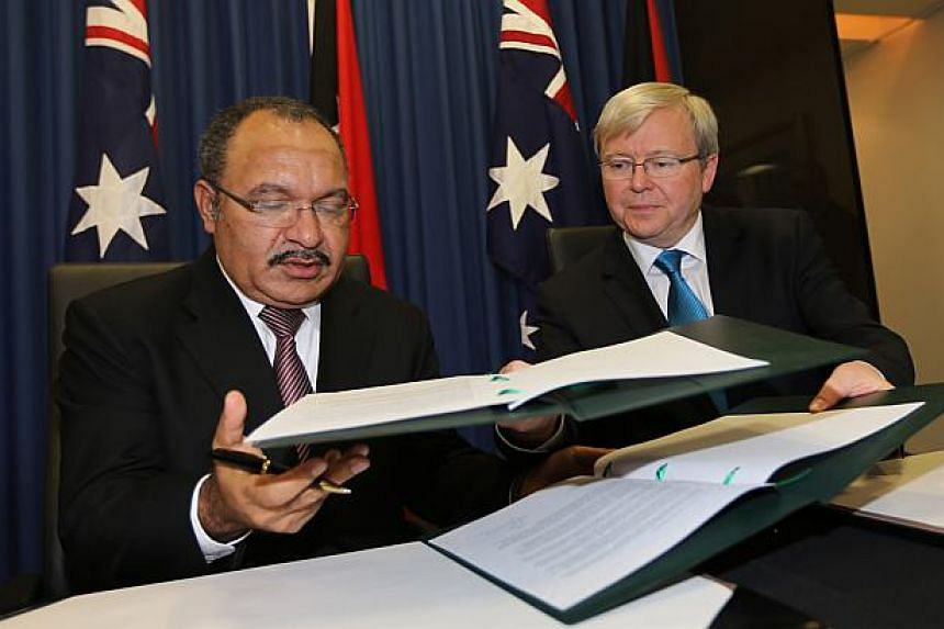 Australian Prime Minister Kevin Rudd, (R) and Papua New Guinea's Prime Minister Peter O'Neill (L) exchange documents after signing an agreement during an announcement of a policy on asylum seekers in Brisbane on July 19, 2013. -- PHOTO: AFP